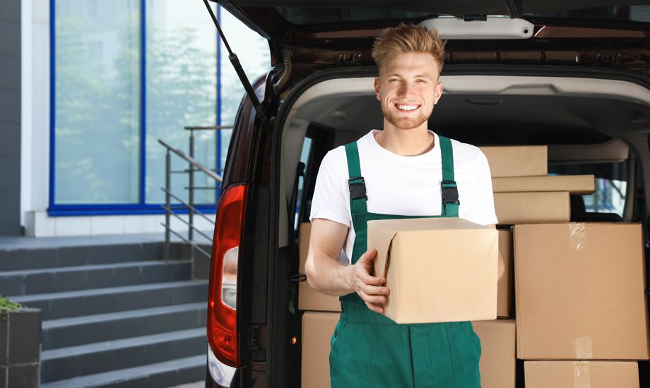 courier and logistics industry finance - courier placing packages in to commercial vehicle