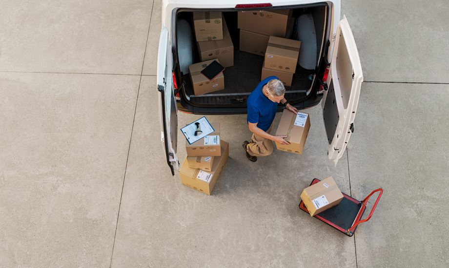 supply chain finance - logistics worker loading packages into a commercial vehicle